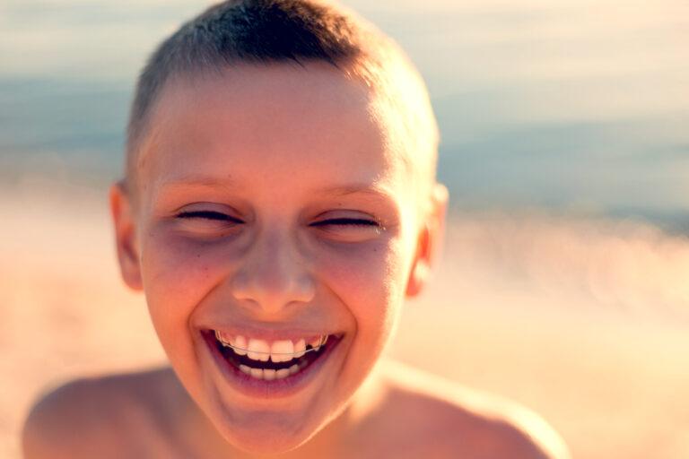 Tween boy smiling in sunlight on the beach