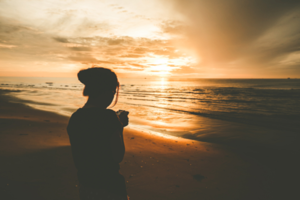 Woman on beach at sunrise