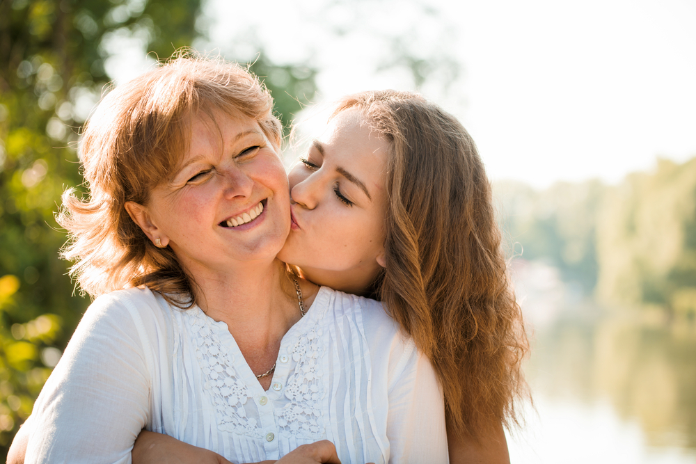 Daughter kissing mother's cheek