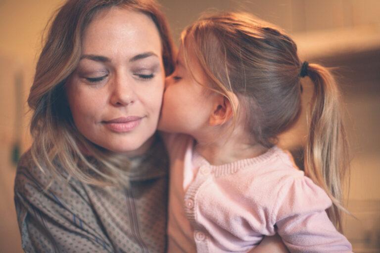 Little girl kissing her mother on the cheek