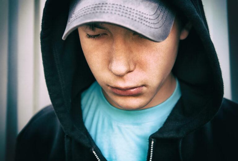 Teen boy in cap looking down