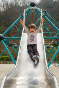 Girl sliding down metal slide