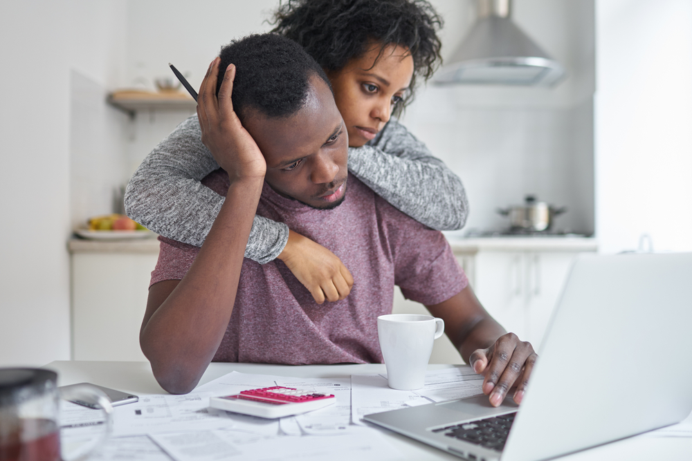 Man stressed looking at computer with woman hugging him