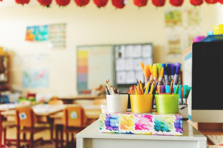 Pencils on teacher desk empty classroom