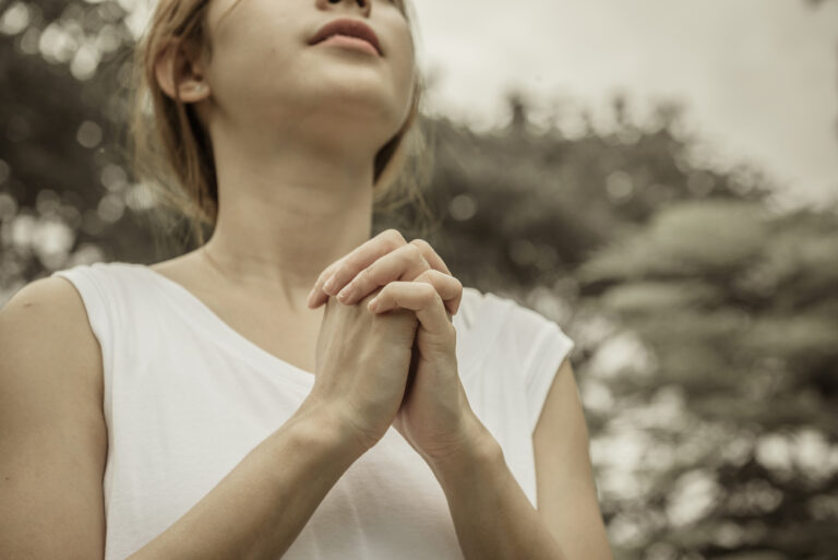 Woman with folded hands praying