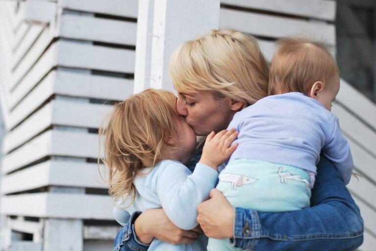Mom kissing two kids
