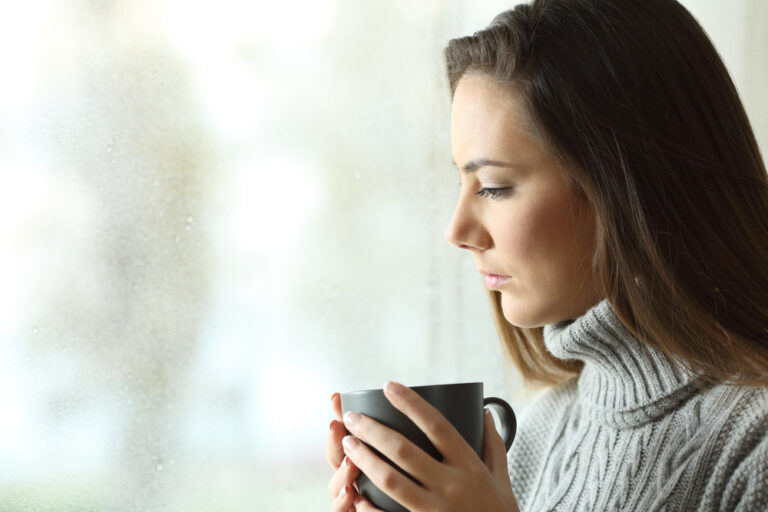 Woman holding coffee cup looking out window
