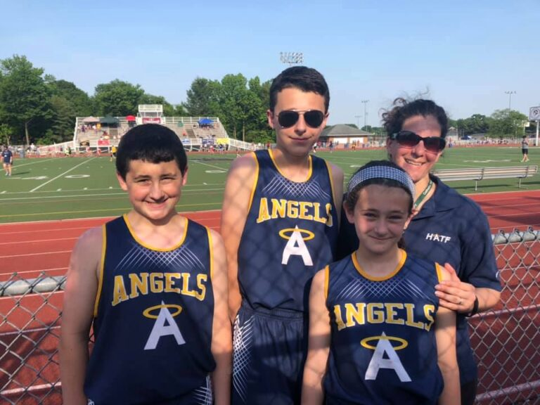 Coach with three young track athletes