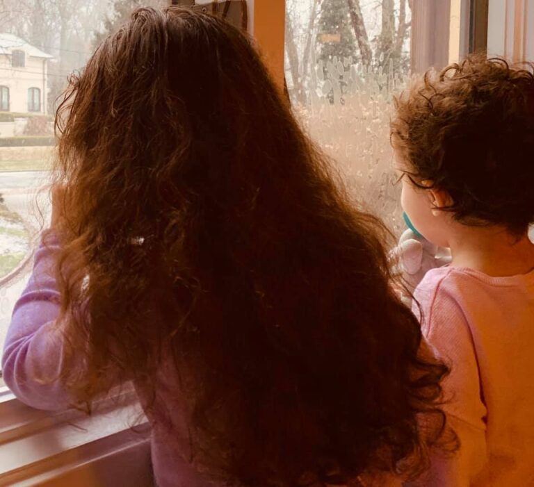 Two girls looking out window