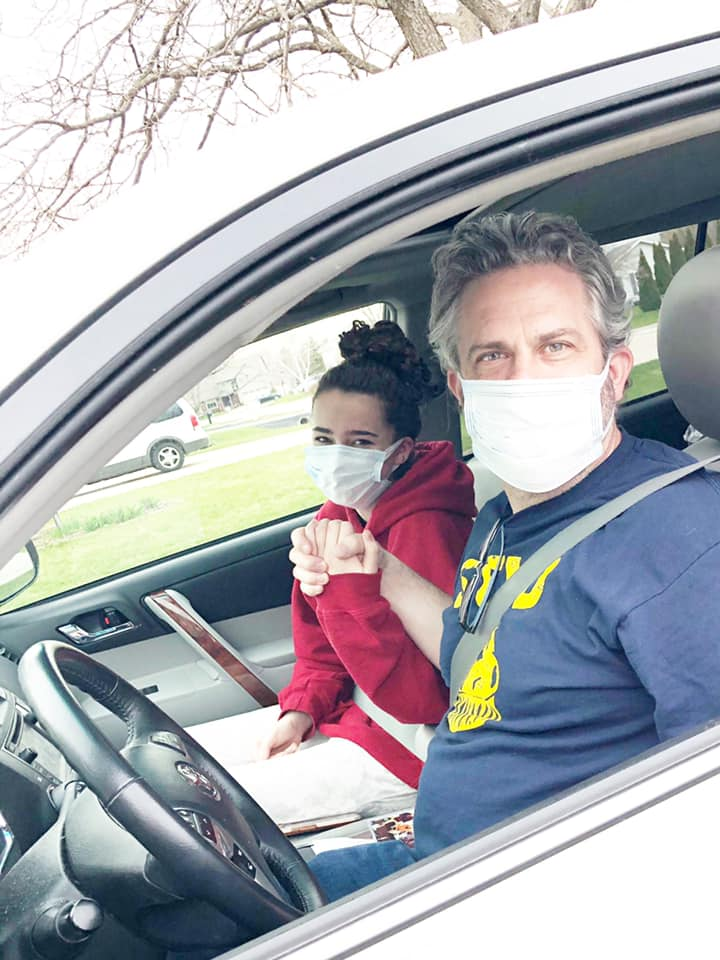 Dad and daughter hold hands in car wearing masks