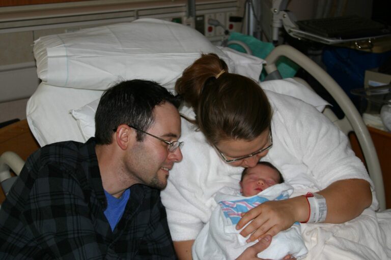 Husband and wife in hospital bed with newborn, color photo
