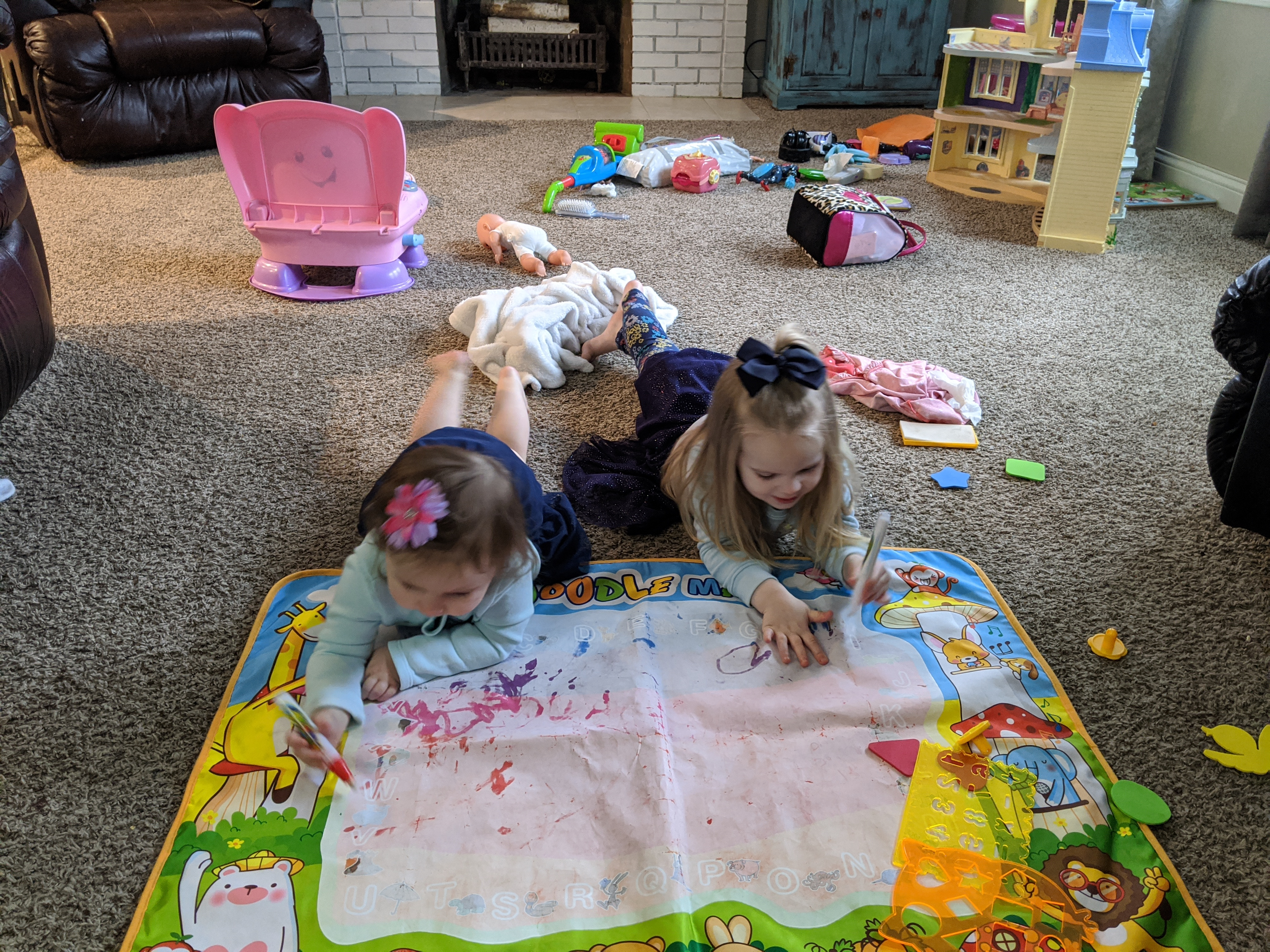 Two young girls lying on the floor with toys scattered, color photo