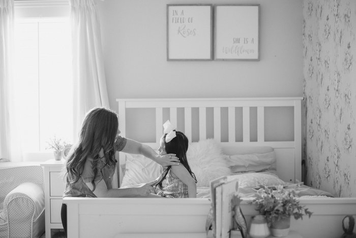 Mom combing daughter's hair, black-and-white photo
