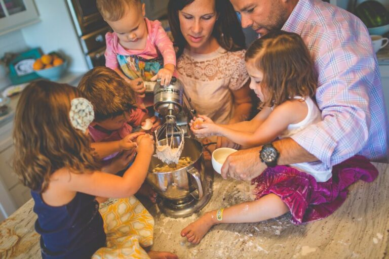 Four children, mother, and father gathered around a kitchen mixer, color photo
