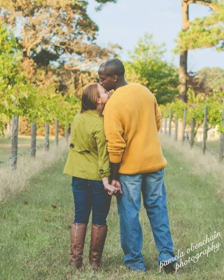 Husband kissing wife's forehead, color photo