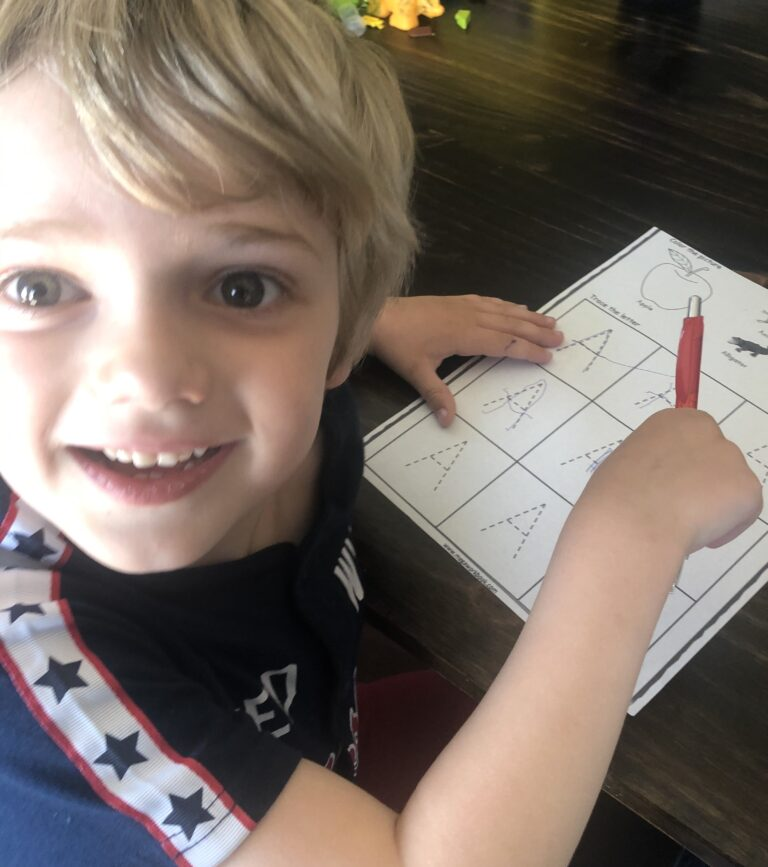 Preschool boy writing paper