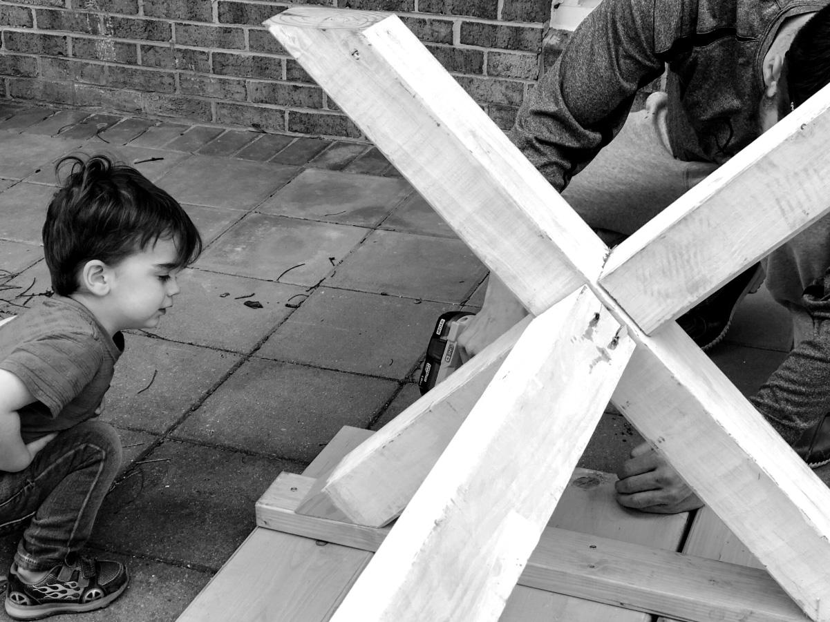 Little boy watching dad build something in backyard