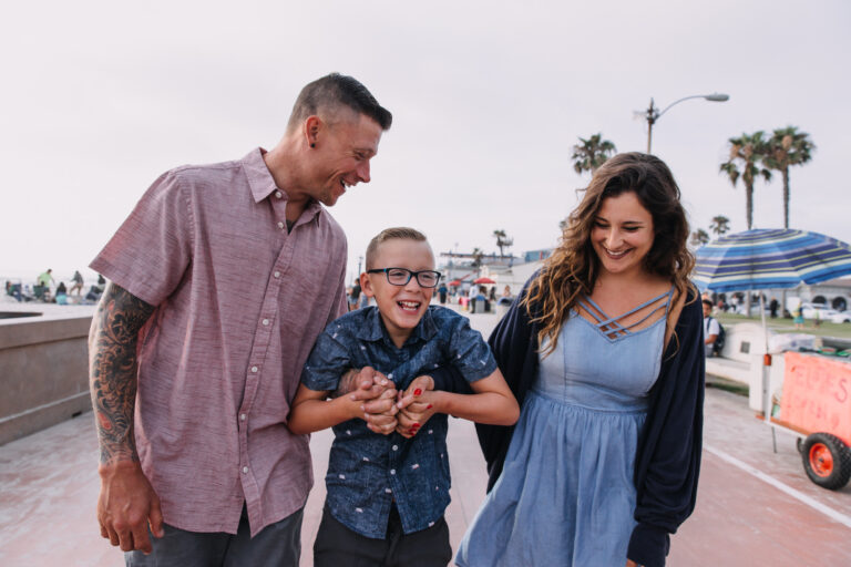 Family of 3 walking and smiling