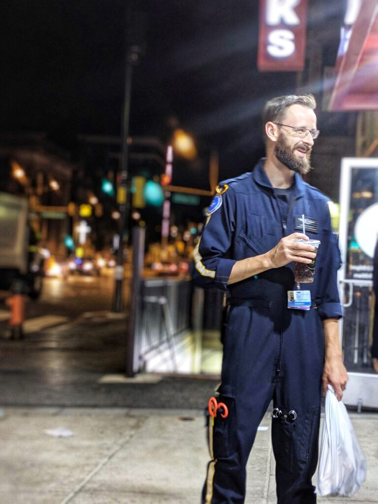 Paramedic standing on street at night