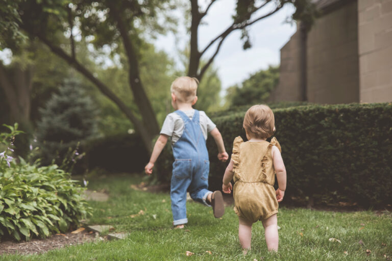 Brother and sister running through yard, color photo