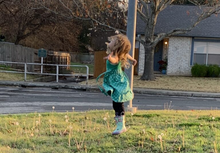 Child standing in the yard, color photo