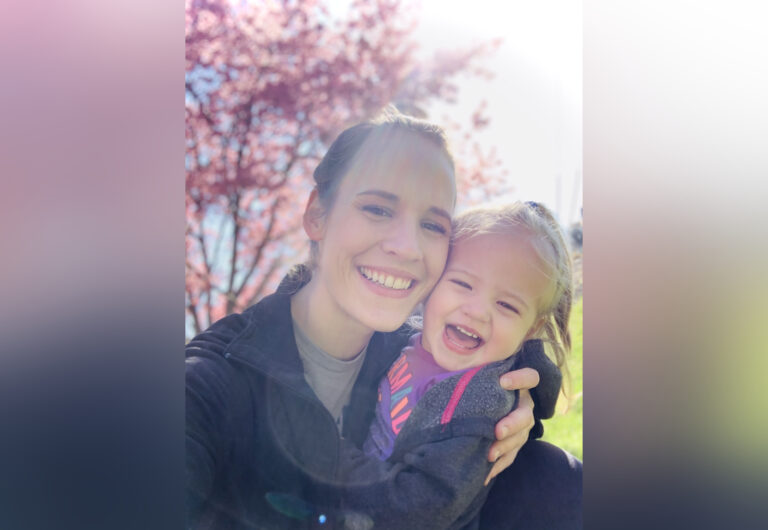 Mom and daughter smiling in sunlight