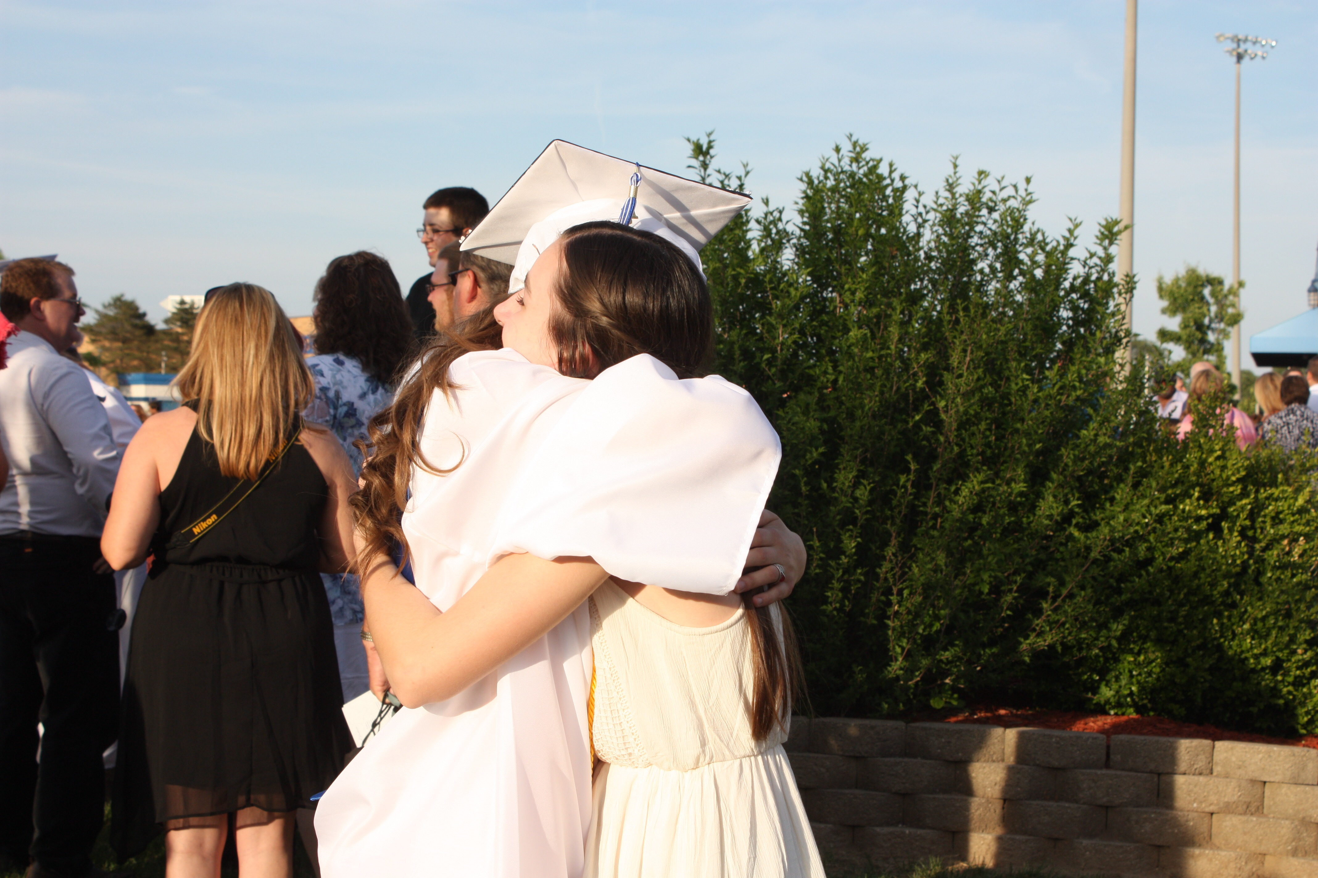 High school graduate hugging sister