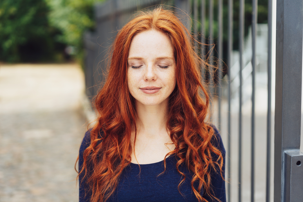 Woman with eyes closed outside