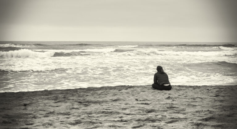Woman sitting by ocean alone