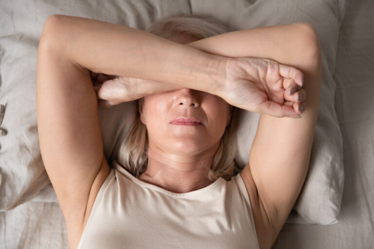 Woman lying down with arms crossed over eyes