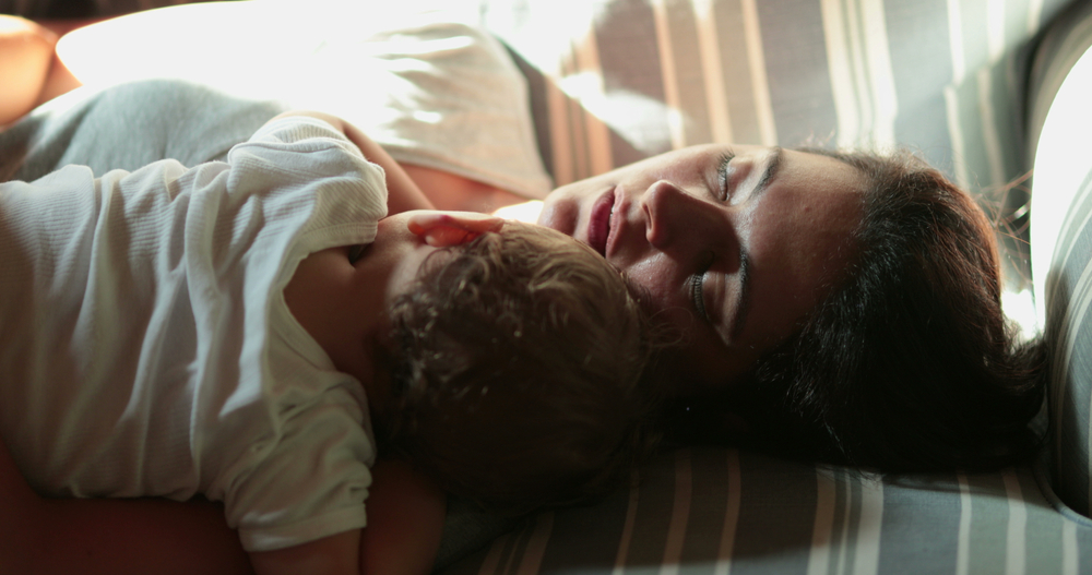 Tired mom with newborn asleep