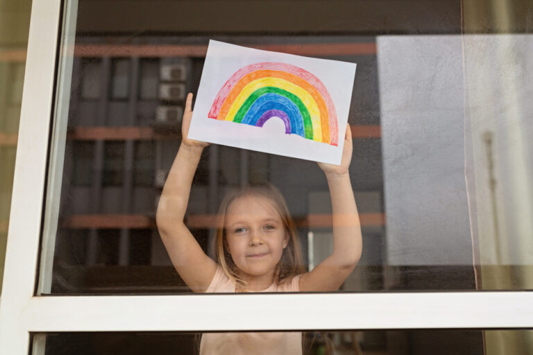 Child holding drawn rainbow to window