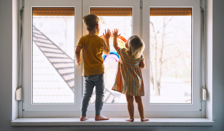 Kids looking out window with rainbow