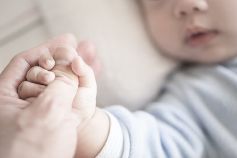 Parent holding baby's hand