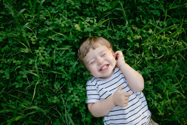 Little boy in grass laughing