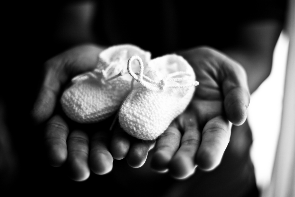 Black and white hands holding baby booties