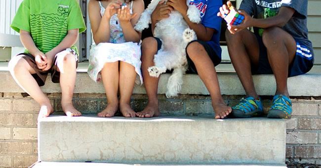 Kids of various skin colors sit on step