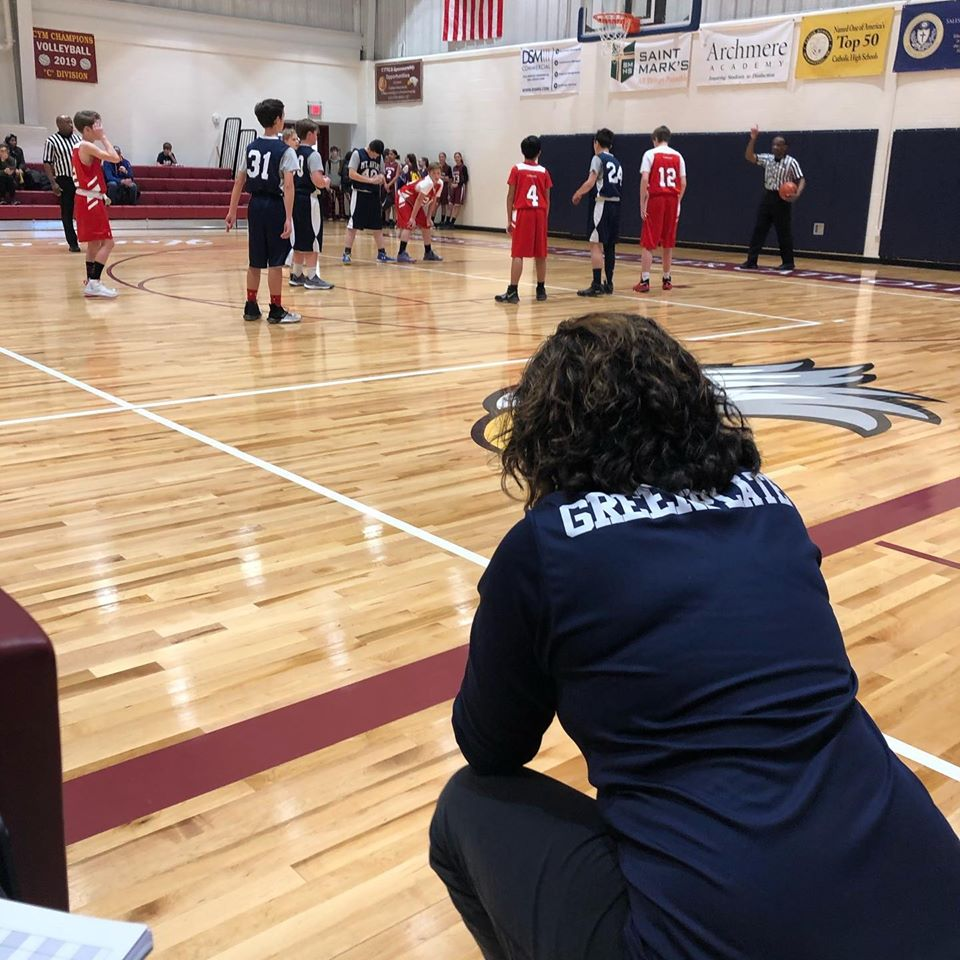 Coach watching youth basketball team