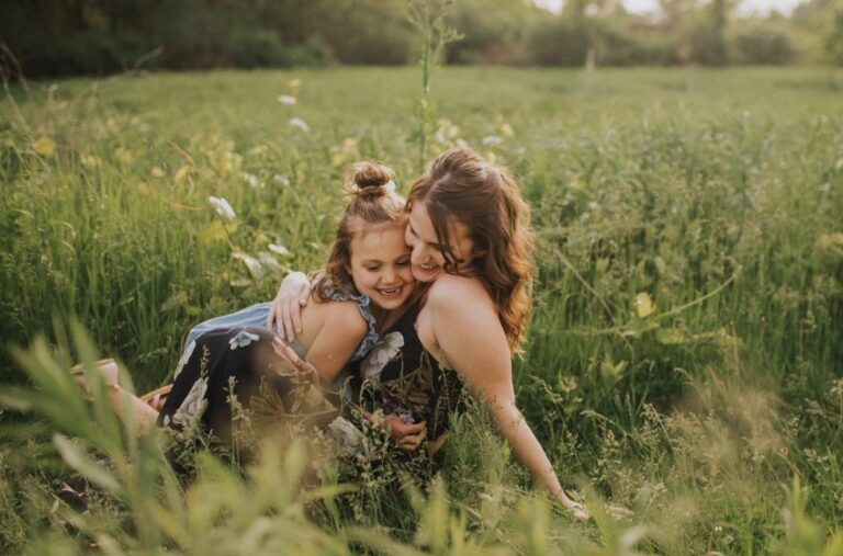 Mother and daughter in a field of grass, color photo