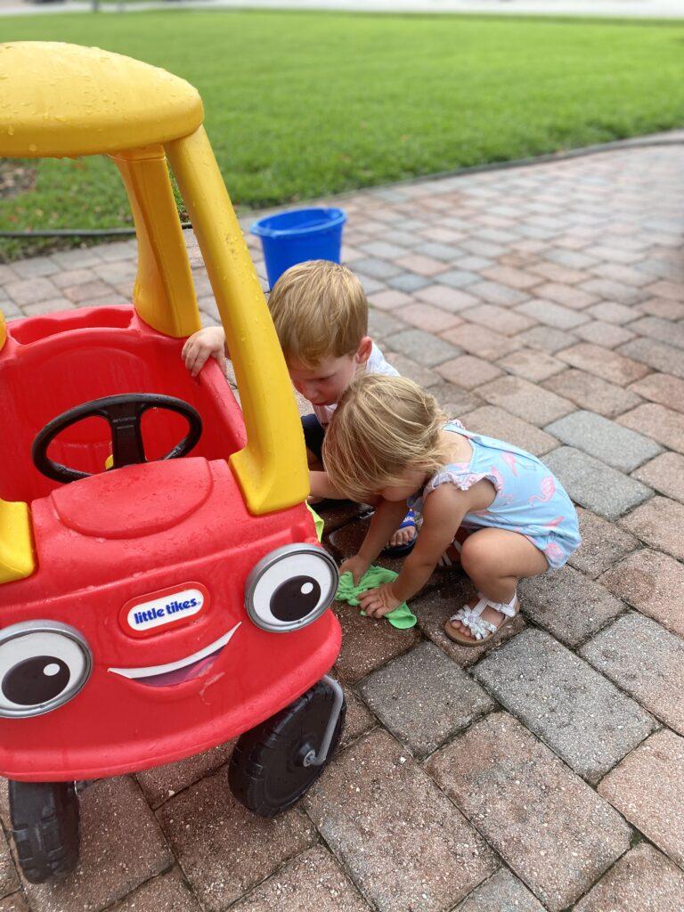 Toddlers washing toy car