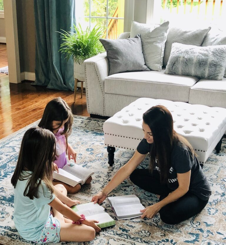 Mom and girls read Bibles in living room