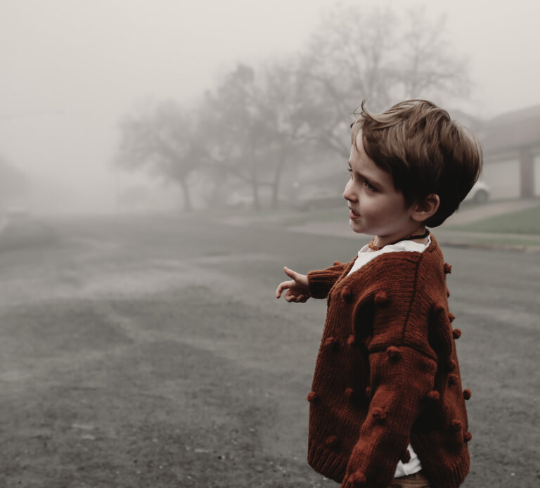 Little boy standing in fog, color photo