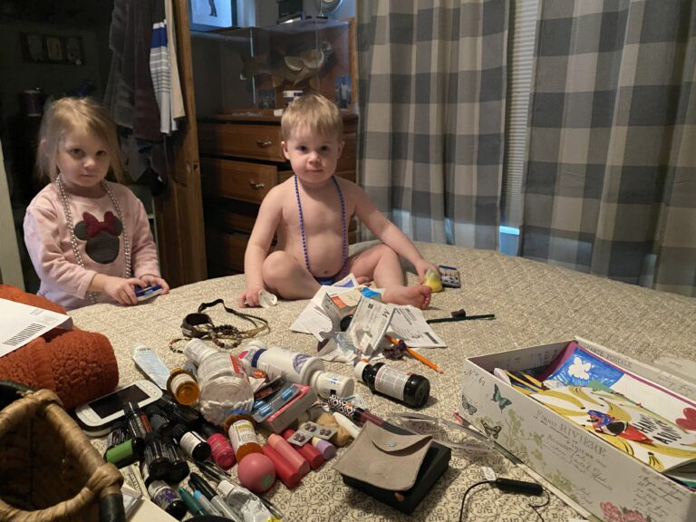 Little boy and girl sitting in the middle of a mess, color photo