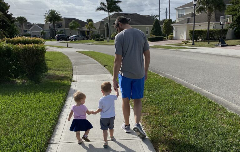 Daddy walking down sidewalk with toddler son and daughter, color photo