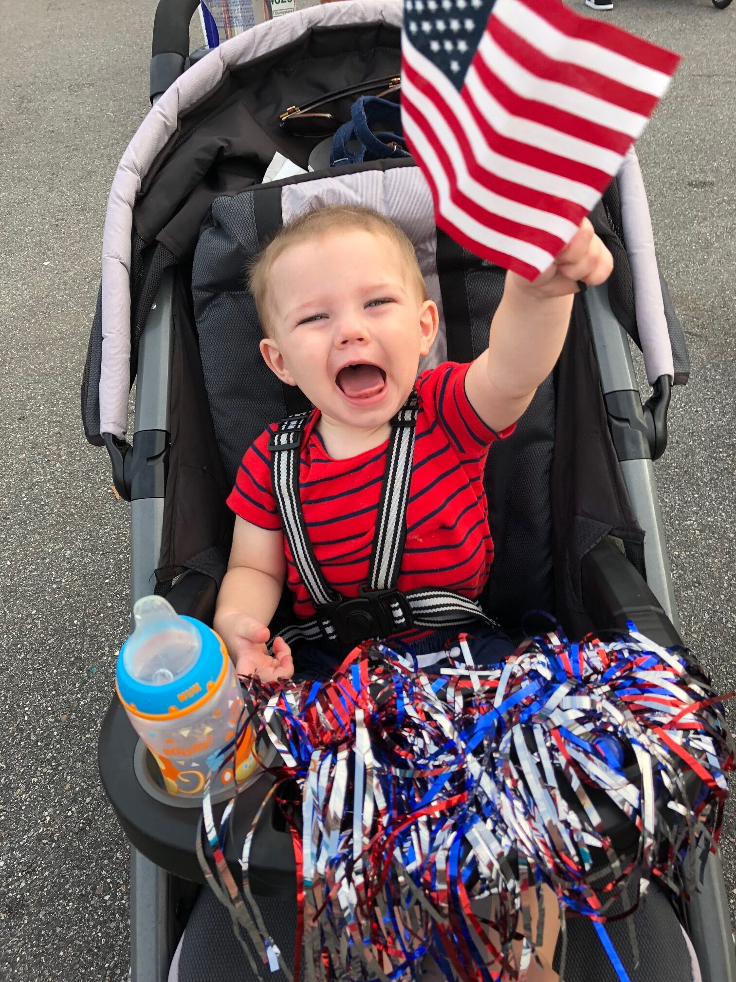 Baby in stroller holding an American flag, color photo