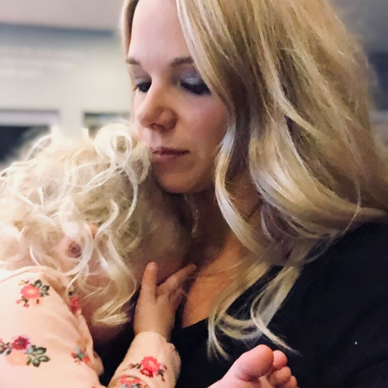 Little girl crying into mom's shoulder, color photo