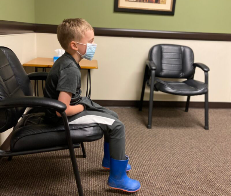 Child sitting in doctor's office while wearing a mask