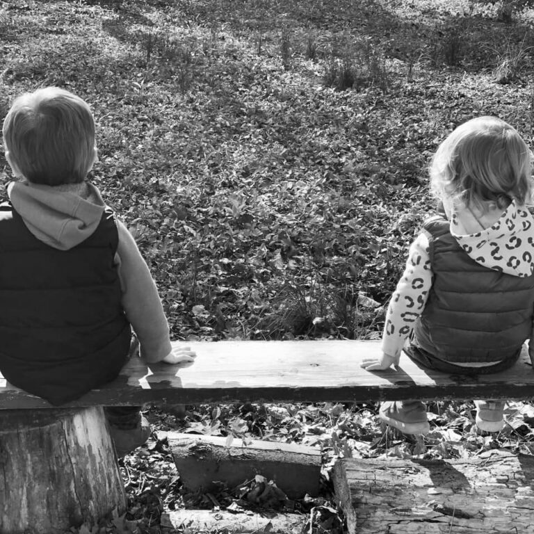 Two kids sitting on bench black and white photo