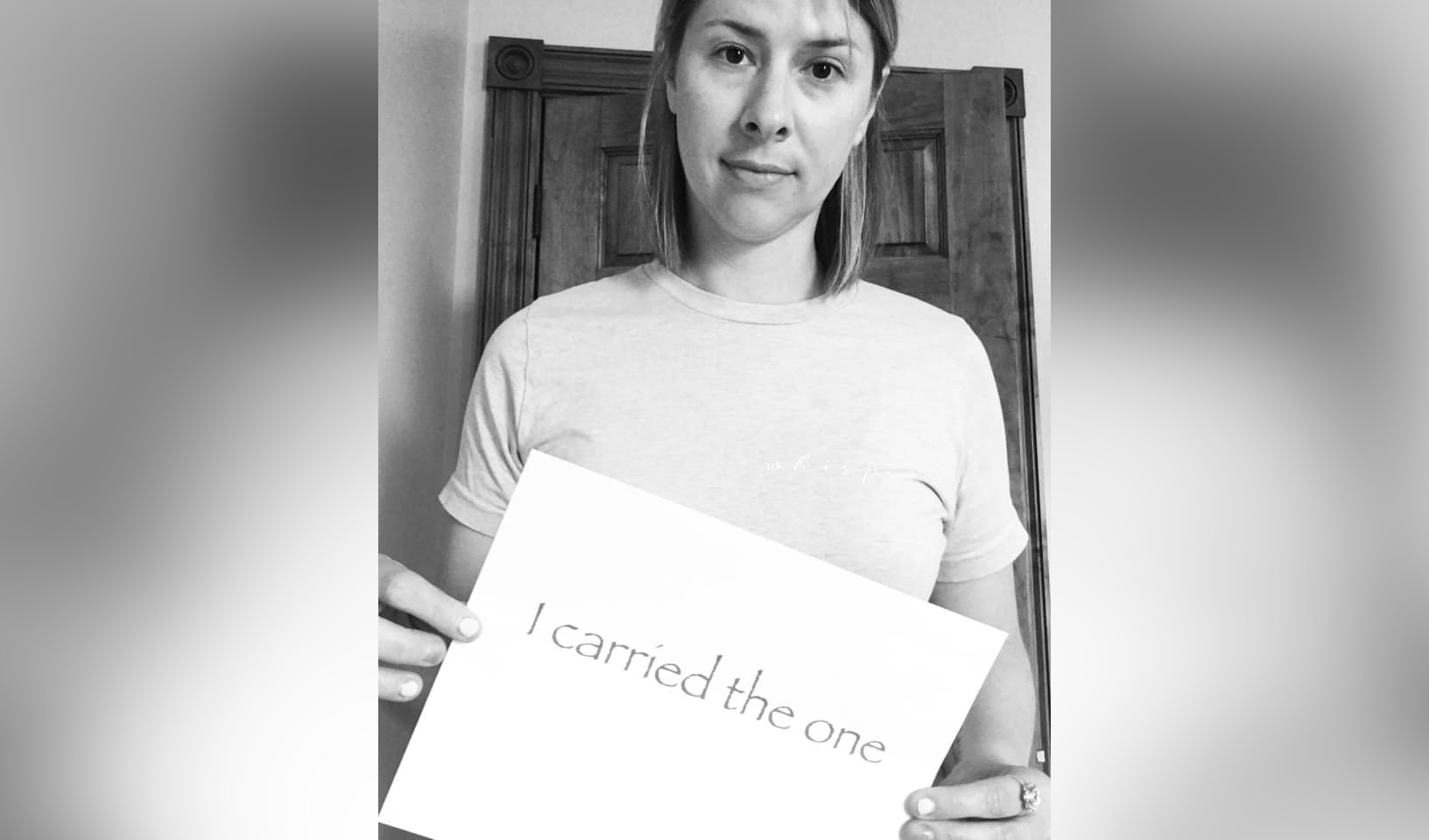 Black and white photo, woman holding sign that says I carried the one
