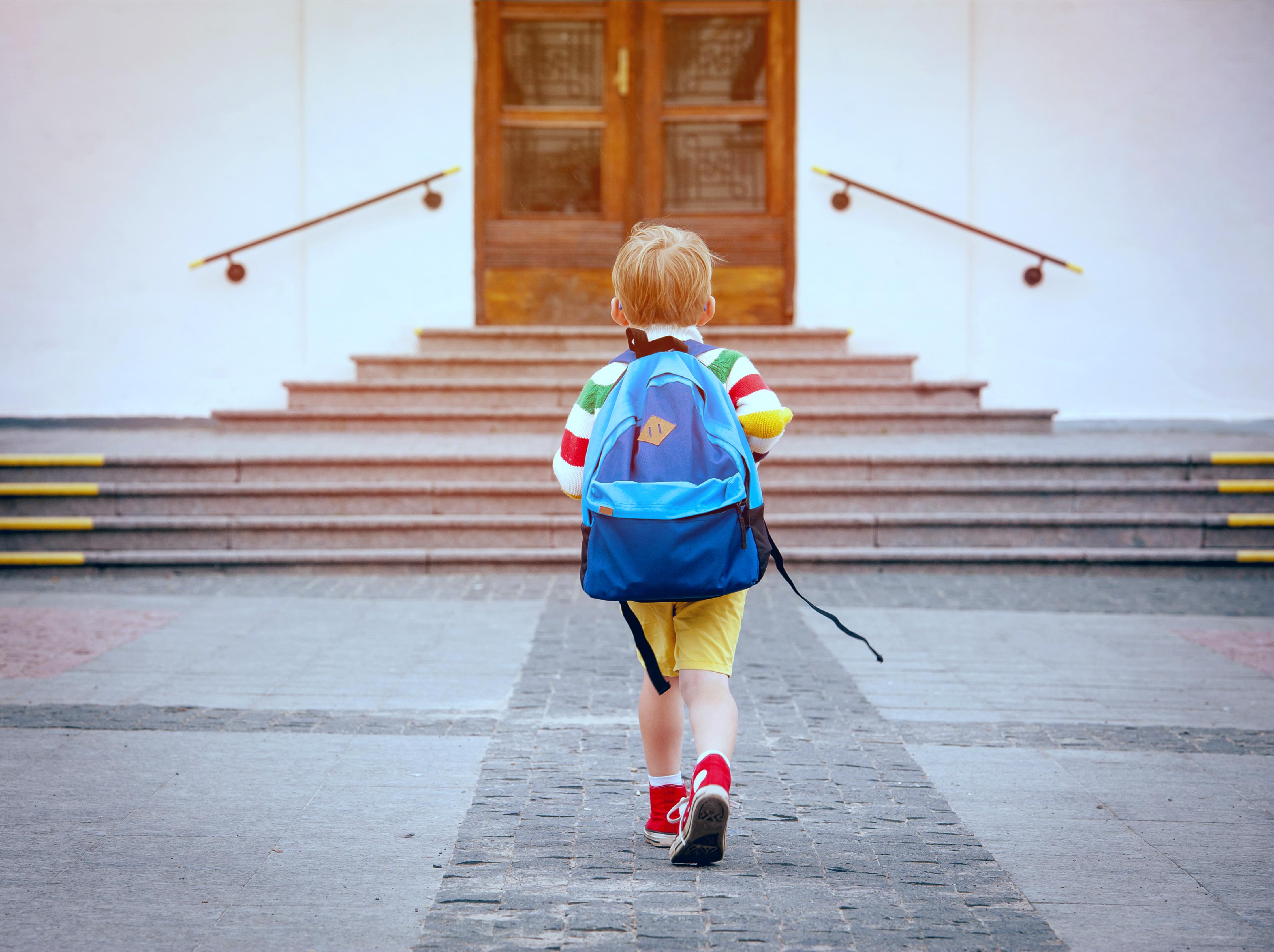 Boy running to school steps